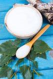 Xilitol - substituto del azúcar Azúcar del abedul en fondo de madera azul Imagen de archivo