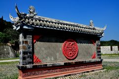 Xin Xing Chen, China: Ceremonial Wall. Xin Xing Zhen, China:  Traditional ceremonial wall with terra cotta dragon medallion and carved stone dragon roof figures Stock Photography