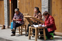 Xin Xing Zhen, China: 3 Women Knitting. Three women seated on bamboo chairs at work knitting and doing needlepoint on the sidewalk in front of an old building in Royalty Free Stock Image