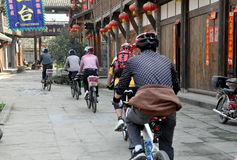 Xin Xing Zhen, China: Bikers Riding in Town. A Sunday bicycling club pedals past the charming old wooden houses hung with red Chinese lanterns on the main street Royalty Free Stock Photos
