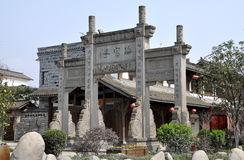 Xin Xing Zhen, China: Ceremonial Gate. An carved ceremonial entrance gate with bas relief dragons and inscribed Chinese characters welcomes people to the old Royalty Free Stock Photography
