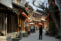 Xin Xing Zhen, China: Handsome Old Houses. View along the old town's main street lined by handsome stone and wooden half-timbered houses hung with red Chinese Royalty Free Stock Image