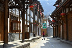 Xin Xing Zhen, China: Handsome Old Houses. Woman walking on a village street lined with handsome half-timbered and stucco houses hung with red Chinese lanterns Stock Image