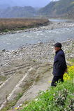 Xin Xing Zhen, China: Man Gazing at River. Standing on terraced banks, an elderly man stares dreamily  at the rock-filled Jing Jiang River as it flows past the Royalty Free Stock Photos