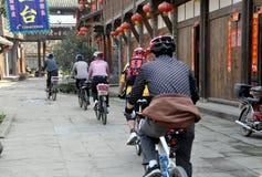 Xin Xing Zhen, China: Radfahrer, die in Stadt reiten Lizenzfreie Stockfotos