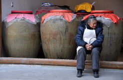 Xin Xing Zhen, China: Woman with Pottery Urns. An old woman sitting in front of three giant pottery urns used for fermenting wines and vinegars at a shop in the Royalty Free Stock Photo