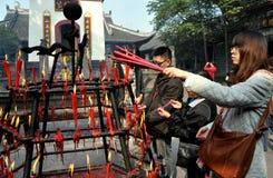Xindu, China: Palillos del incienso de la iluminación en el templo Foto de archivo