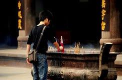 Xindu, Chiny: Mężczyzna oświetlenia kadzidła kije Zdjęcia Stock