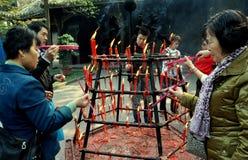 Xindu, Cina: Bastoni di incenso di illuminazione della gente Fotografie Stock
