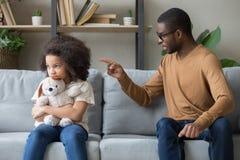 Xingamento africano do paizinho para a filha teimoso da disciplina que senta-se no sofá foto de stock royalty free