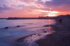Xinghai Beacht på den röda kulöra solnedgången reflekterade i havet, Dalian, Kina Arkivbilder