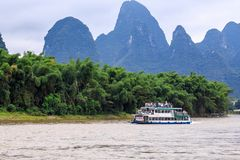 A pleasure boat is floating along the Li River known as well as Lijiang River who is in Xinping Town of China stock image