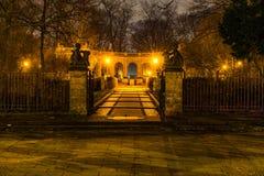 XIX对一个公园的世纪入口在晚上 库存图片