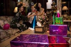 Xmas党的礼物盒与快乐的朋友给多士香槟背景 库存图片