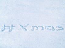 #Xmas切细在蓝色雪写的标记,圣诞节hashtag字法 图库摄影
