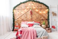 Xmas在早晨卧室 在圣诞节内部的双人床在木墙壁背景 免版税图库摄影