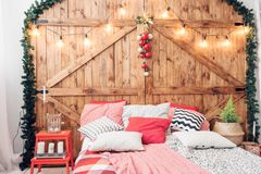 Xmas在早晨卧室 在圣诞节内部的双人床在木墙壁背景 免版税库存图片