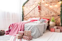 Xmas在早晨卧室 在圣诞节内部的双人床在木墙壁背景 库存照片