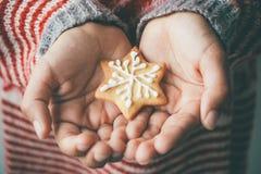 Xmas曲奇饼在儿童手上 库存图片