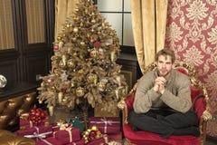 xmas树的强壮男子与当前箱子在客厅 免版税库存照片