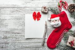 Xmas贺卡 木背景、被绘的白色与圣诞节袜子和圣诞老人 在它上色的糖果 手工制造礼物 库存照片