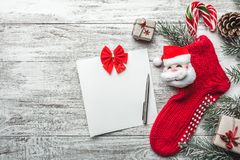 Xmas贺卡 木背景、被绘的白色与圣诞节袜子和圣诞老人 在它上色的糖果 手工制造礼物 图库摄影