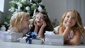 Xmas,有说谎在近地板上的卷发的可爱的女朋友在背景装饰的圣诞树提出 股票视频