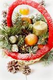 葡萄酒圣诞节或xmas构成 篮子用蜜桔、杉木锥体、金黄球、冷杉分支和蜡烛 免版税库存照片