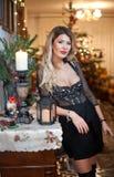 典雅的黑礼服的美丽的性感的妇女有Xmas树的在背景中 画象时兴白肤金发女孩摆在室内 免版税库存照片