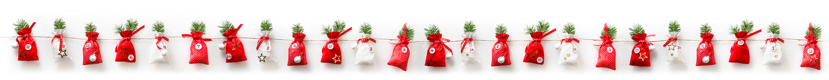 Xmas Advent calendar stuffed 24 sachets in a row. Hanging on a rope isolate on white background for christmas season stock image