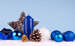 Xmas background. Christmas decoration - candles, xmas balls , oak ball and star on snow Royalty Free Stock Photography