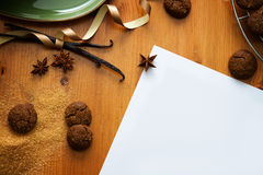 Xmas background. Baking background with ginger cookies and empty paper on wooden table, top view Stock Photos
