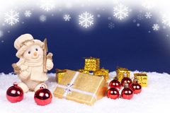 Xmas background - blue with flakes. Golden snowman figure and red , gold xmas balls royalty free stock image