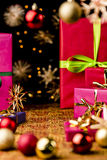 Xmas Background with Gifts, Stars and Spheres. Presents in solid, vibrant colors with bows. Blurred Christmas bulbs and stars outside the shallow depth of field Stock Photography