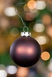 Xmas ball 9. Xmas ball with a out of focus christmas tree in the background Royalty Free Stock Photo