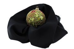 Xmas ball cradled on a black cloth. Xmas decorative ball resting and wraped by a black cloth isolated on a white background Stock Photography