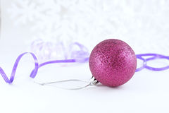 Xmas ball with snowflakes. Xmas ball on soften light snowflakes background with color ribbon Stock Images