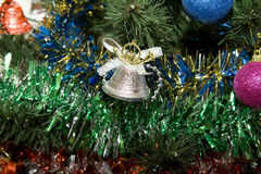 Xmas Balls. Silvery hand bell a sphere on a celebratory tree stock photography