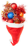 Xmas balls and decoration spillover from santa hat Royalty Free Stock Images