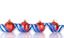Xmas balls and ribbon. Four red xmas balls between blue shiny ribbon Royalty Free Stock Photo