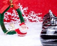Xmas balls and santa claus figure. Xmas coronet on snow with xmas balls beside Royalty Free Stock Photos