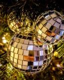 Xmas Bauble reflecting on the tree. A shiny mirror bauble reflecting the lights on the xmas tree Stock Photos