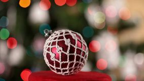 Xmas bauble spinning and sliding in front of blurry christmas tree stock video