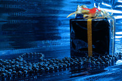 Xmas blue wrapped present and beads on blue Stock Photo