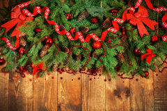 Xmas border. Christmas Border - fir branches with red baubles, bells and snowflakes on a wooden background royalty free stock photography