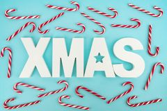 XMAS. Candy Canes and wooden XMAS Letters on blue light background stock photo
