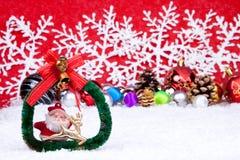 Xmas card. Xmas coronet on snow with xmas balls in background Royalty Free Stock Photography
