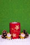 Xmas card. Candle between two golden santa clause figures and oak balls Royalty Free Stock Images