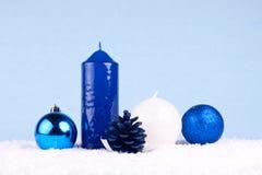 Xmas card. Candles, xmas balls and oak ball on snow Stock Photos