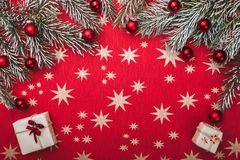 Xmas card, red background with stars. Space for your text. Fir branches with red balls. Top view.  royalty free stock photo
